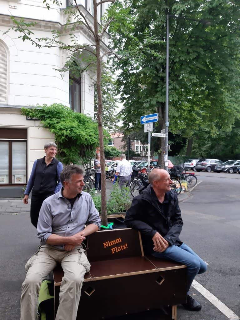 """Das Wanderbaummodul auf der Straße. Zwei Personen sitzen auf der Sitzfläche um den Baum herum. Zwischen den beiden ist der Schriftzug """"Nimm Platz!"""" auf der Rückenlehne. Hinter dem Modul steht eine dritte Person. Alle drei schauen nach rechts und lachen."""